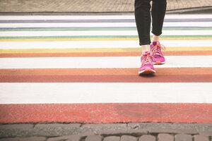 Woman crossing multi coloured zebra crossing, partial view - CHPF000287