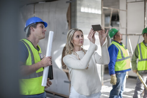 Construction workers and woman on construction site - ZEF009447