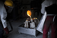 Worker casting metal in a foundry - ZEF009469