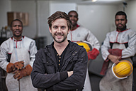 Portrait of smiling man standing in front of staff - ZEF009487