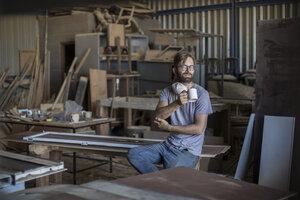 Carpenter drinking coffee in workshop - ZEF009516