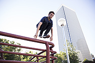 Spain, Madrid, man jumping over a fence in the city during a parkour session - ABZF000989