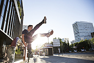 Spain, Madrid, man jumping over a fence in the city during a parkour session - ABZF000998