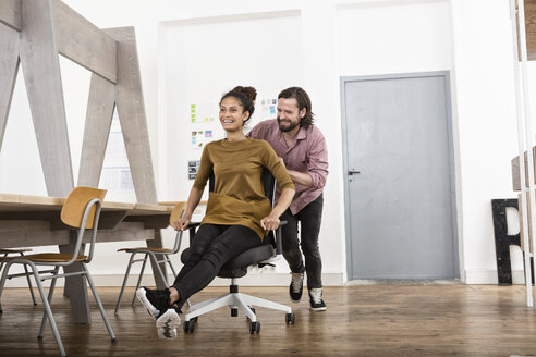 Man pushing happy woman on office chair - RBF004922