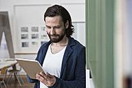 Man using digital tablet in office - RBF004925