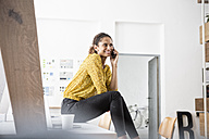Smiling woman sitting on office desk using cell phone - RBF004937