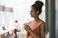 Smiling woman in office holding cup of coffee - RBF004949