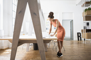 Woman standing at office desk using laptop - RBF004952