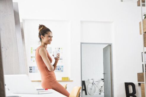Smiling woman in office holding cup of coffee - RBF004955