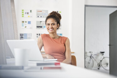 Smiling woman sitting at office desk using laptop - RBF004958