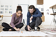 Two colleagues on office floor looking at construction plan - RBF004976