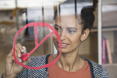Woman drawing symbol on glass pane in office - RBF004979