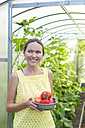 Happy woman with bowl of harvested tomatoes in front of greenhouse - KNTF000443