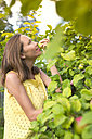 Woman smelling apple in the garden - KNTF000461