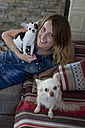 Smiling woman with her dogs on the couch at home - MAUF000815