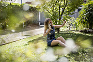 Woman taking selfie with her Chihuahua in the garden - MAUF000821