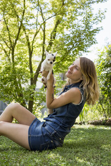 Happy woman sitting on meadow in the garden with her Chihuahua - MAUF000824