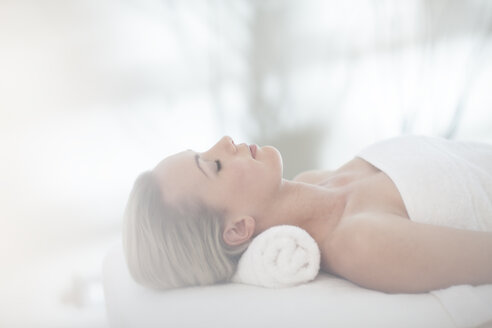 Young woman lying on massage table at spa - ZEF009570