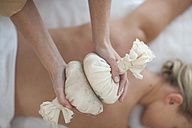 Masseuse holding aromatherapy sachets over woman's back - ZEF009594