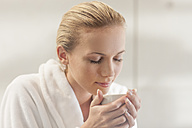 Young woman in bathrobe drinking tea - ZEF009603
