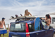 Friends with surfboards on car at the coast - ZEF009615