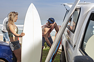 Friends taking out surfboards from car at the coast - ZEF009621