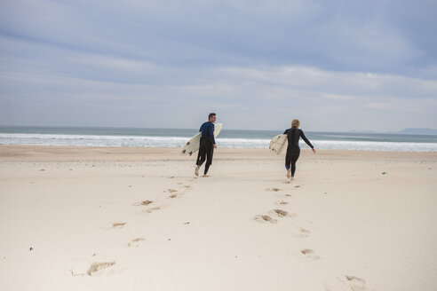 Couple with surfboards on the beach walking to the sea - ZEF009630