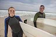 Smiling couple with surfboards on the beach - ZEF009633