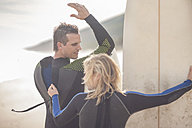 Woman with surfboard zipping man's wetsuit - ZEF009639