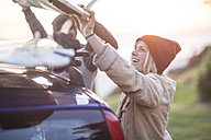 Happy couple putting surfboard on car roof at sunset - ZEF009648