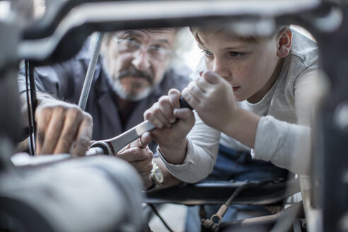 Senior man and boy working on mechanism of a car - ZEF009690