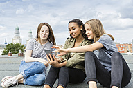 Germany, Berlin, three teenage girls sitting on roof top listening music with earphones - OJF000144