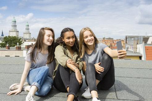 Germany, Berlin, three teenage girls sitting on roof top taking selfie with smartphone - OJF000147