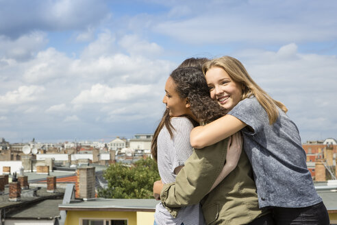 Three happy teenage girls hugging each other on roof top - OJF000150
