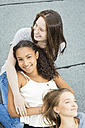 Three teenage girls relaxing together on roof top - OJF000165