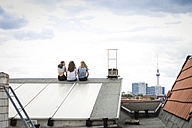 Germany, Berlin, back view of three friends sitting side by side on roof top - OJF000171