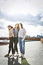Germany, Berlin, three teenage girls standing on roof top - OJF000174