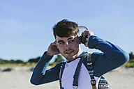 Portrait of young man with headphones on the beach - BOYF000552