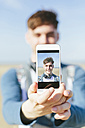 Selfie of smiling young man on display of smartphone - BOYF000555