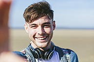 Portrait of smiling young man on the beach - BOYF000558