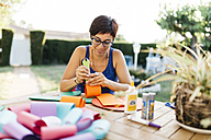 Woman doing handicrafts at garden table - JRFF000838