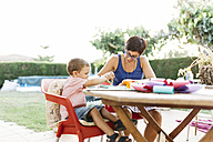 Mother and son doing handicrafts at garden table - JRFF000841