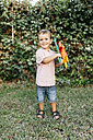 Boy holding home-made cardboard flower in garden - JRFF000850