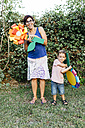 Mother and son holding home-made cardboard flowers - JRFF000853