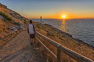 Italy, Apulia, Salento, Capo d'Otranto, man admiring the sunrise at lighthouse - LOMF000335