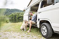 Man with dog in a van at lakeside - FMKF002781
