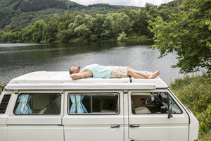 Man lying on roof of a van at lakeside - FMKF002787