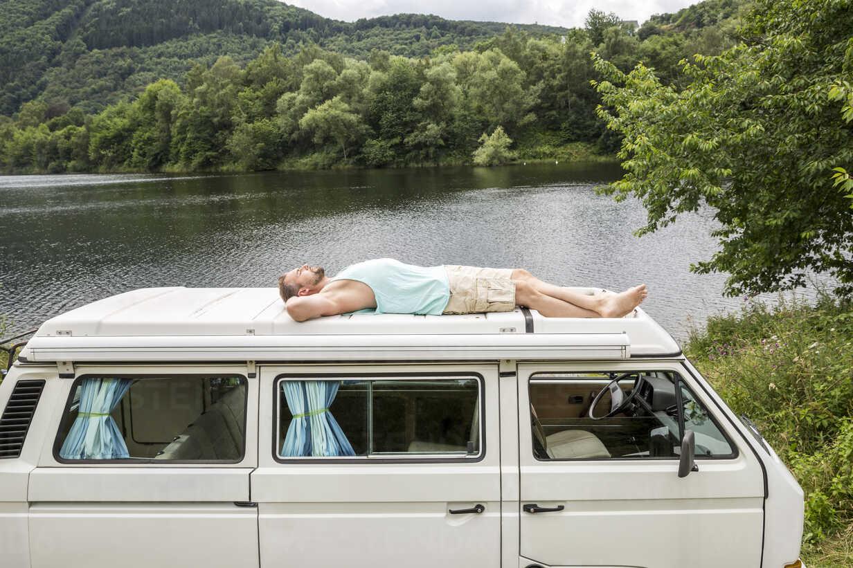 Man lying on roof of a van at lakeside - FMKF002787 - Jo Kirchherr/Westend61