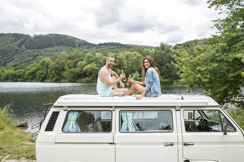Couple clinking beer bottles on roof of a van at lakeside - FMKF002793