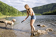 Young woman playing with her dog in a lake - FMKF002796